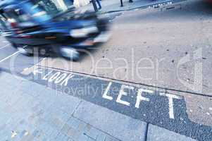 Lokk left sign on a London street with taxi cab fast approaching