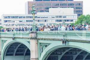 LONDON - AUG 23, 2013: Tourists walk along Westminster Bridge. L