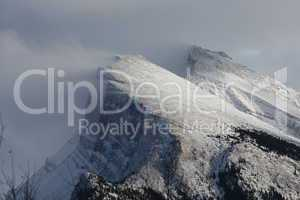Snow blowing off the top of a mountain ridge in the rockies