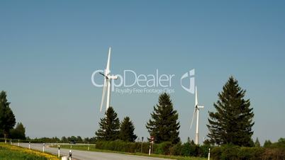 Two windmills and pine trees beside the road FS700 4K Odyssey7Q