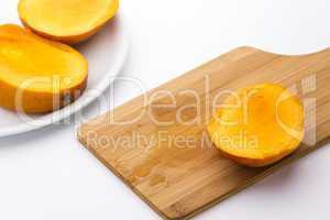 Third Of A Mango And Its Juice On Wooden Board