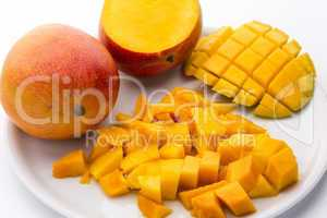 Heap Of Juicy Mango Cubes And Whole Fruit On Plate