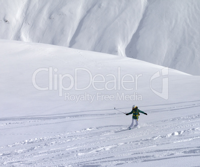 Snowboarder downhill on off piste slope with newly fallen snow