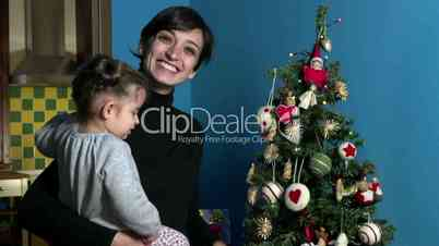 Happy Mother And Daughter Looking At Christmas Tree At Home