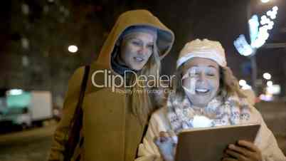 Two women walking with pad outdoor in the cold evening