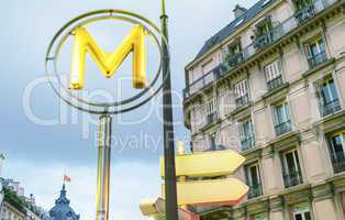 Subway sign in Paris with city building. Metro