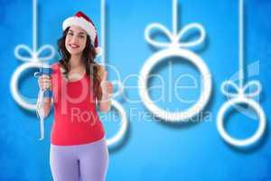Composite image of festive fit brunette holding measuring tape a