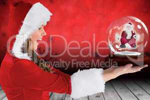 Composite image of sexy santa girl holding snow globe