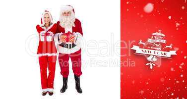 Composite image of santa and mrs claus smiling at camera offerin