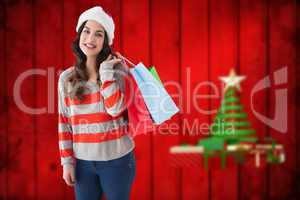 Composite image of beauty brunette posing with shopping bags