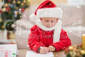 Composite image of festive little boy writing wish list