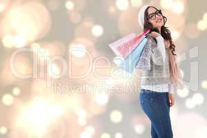 Composite image of brunette with glasses holding shopping bags