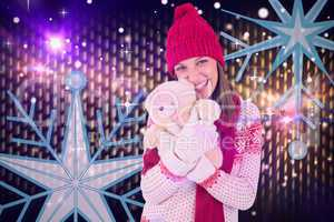 Composite image of cute brunette in warm clothing hugging teddy