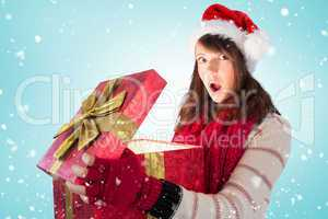 Composite image of young woman opening a glowing christmas gift