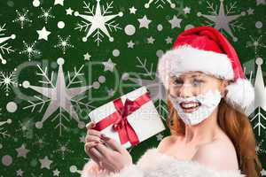 Composite image of festive redhead in foam beard holding gift
