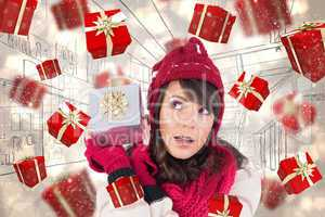 Composite image of young woman shaking her gift in order to gues