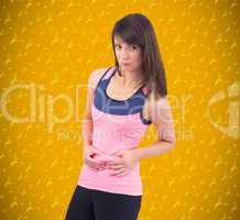 Composite image of festive fit brunette pinching her stomach