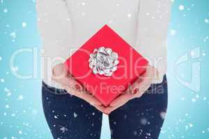 Composite image of woman with nail varnish holding red gift