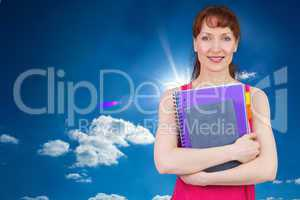 Composite image of woman holding her school notebooks