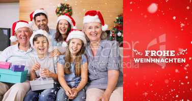 Composite image of extended family in christmas hats with gift b
