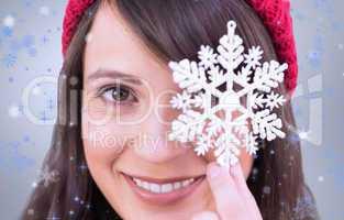 Composite image of festive brunette holding snowflake decoration