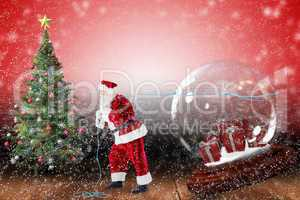Composite image of santa pulling snow globe of presents