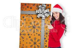 Composite image of smiling brunette in santa hat pointing gift c