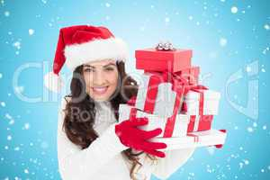 Composite image of festive brunette in santa hat holding pile of
