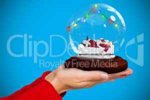 Composite image of hand holding santa snow globe