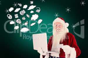 Composite image of santa pays with credit card on a laptop