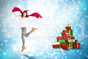 Composite image of happy brunette jumping and holding his scarf
