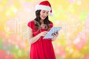 Composite image of festive brunette using her tablet pc