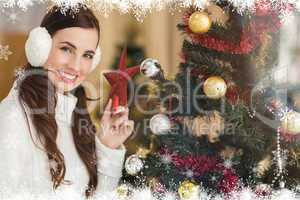 Composite image of smiling brunette holding star near a christma