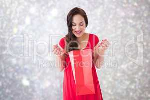 Composite image of stylish brunette in red dress opening gift ba