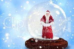 Composite image of santa holding open sack snow globe