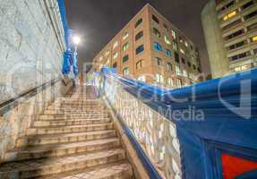 Stairs of Tower Bridge at night with surrounding buildings, Lond