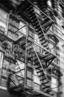 Motion blurred image of New York brick buildings with outside fi