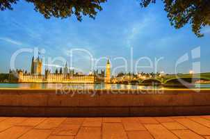 Houses of Parliament framed by trees and boardwalk at dusk - Lon