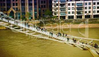 LONDON - SEPTEMBER 27, 2013: Tourists walk on Millennium Bridge.