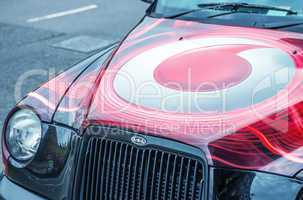 LONDON - SEPTEMBER 27: A taxi cab decorated with Vodafone brandi