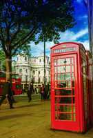 LONDON - SEPTEMBER 27, 2013: Tourists walk in front of a red pho