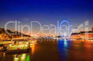 London night skyline along river Thames. Panoramic wheel, buildi