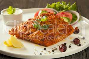 Grilled fish tikka served on a plate with salad and tarter sauce