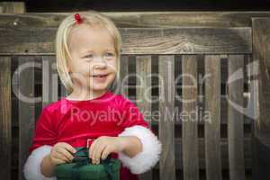 Adorable Little Girl Unwrapping Her Gift on a Bench