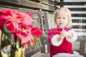 Adorable Little Girl Sitting On Bench with Her Candy Cane