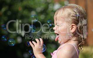 Happy little girl playing with soap bubbles in the garden