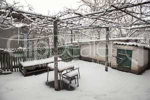 snowy rural courtyard with homemade table, chairs and bench
