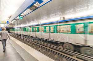 Blurred picture of moving business man in Paris Metro with train