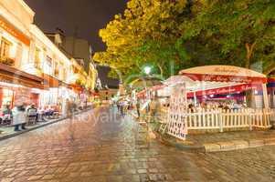 PARIS - JUNE 20, 2014: Tourists explore Montmartre streets at ni