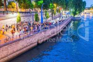 PARIS, FRANCE - JULY 21, 2014: Tourists walk along Seine River o